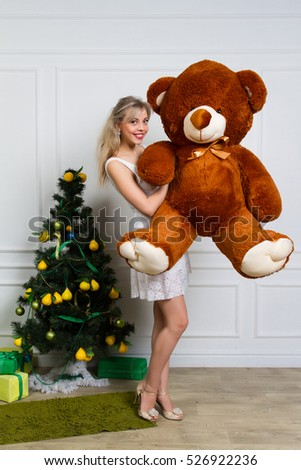 Happy woman received a teddy bear. Her beautiful eyes looking at camera. Concept of holiday, christmas.