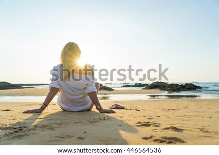Happy woman  relaxes and enjoys the sunset over the sea sitting on the beach - stock photo
