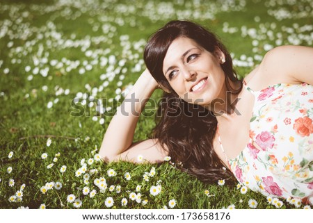 Happy woman relaxing and day dreaming lying down on grass and daisies in park outdoors. Beautiful girl natural portrait. - stock photo