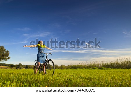 Happy woman relaxing and sitting on a bicycle, in a green meadow - stock photo