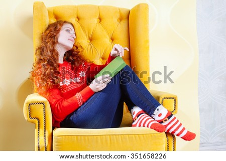 Happy woman relaxing at home and reading a book on yellow chair