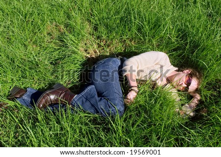 Happy woman relaxing on grass in park. Shot in Vergelegen estate, near Cape Town, Western Cape, South Africa. - stock photo