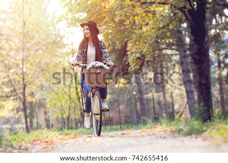 Happy woman riding bike bicycle in fall autumn park