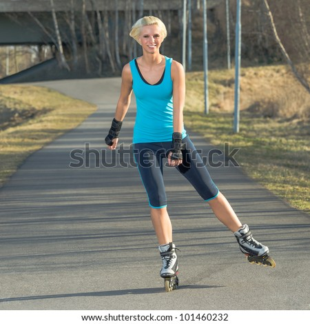 Happy woman roller skating sport smiling in park sunny day