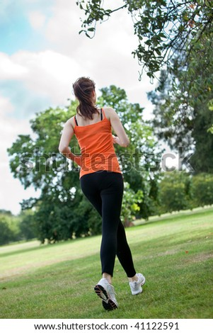 Happy woman running at the park with sportswear - stock photo
