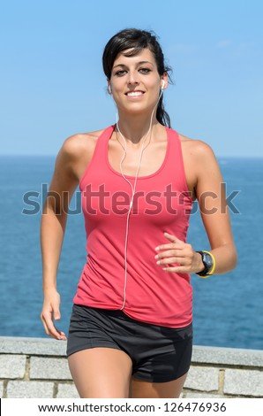 Happy woman running on summer. Female caucasian fitness athlete jogging on sea background. - stock photo