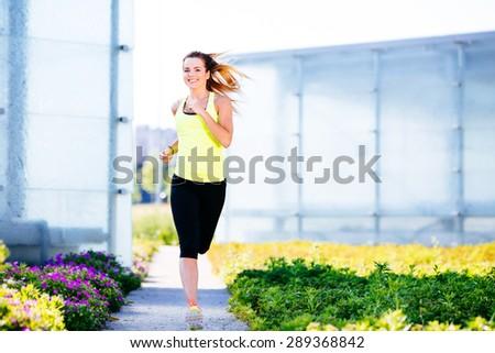 Happy woman running outdoors - stock photo