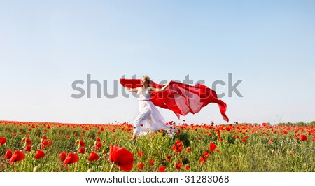 happy woman running with red scarf in poppy field - stock photo