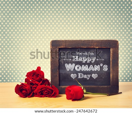 Happy Woman's Day message written on little chalkboard with roses - stock photo