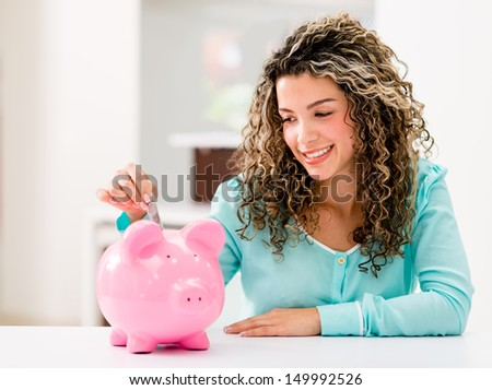 Happy woman saving money in a piggybank  - stock photo