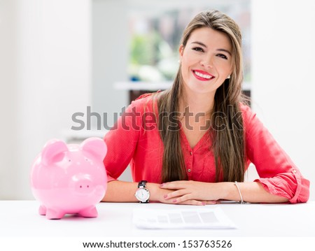 Happy woman saving money in a piggybank  - stock photo