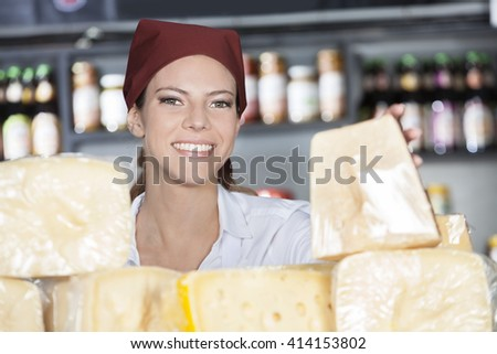 Happy Woman Selling Fresh Cheese In Store - stock photo