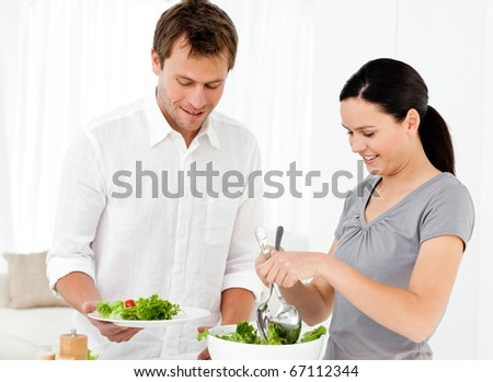 Happy woman serving salad to his boyfriend for the lunch in the kitchen