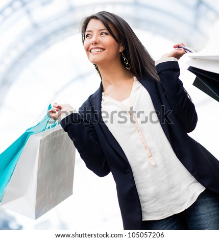 Happy woman shopping and holding bags at the mall - stock photo