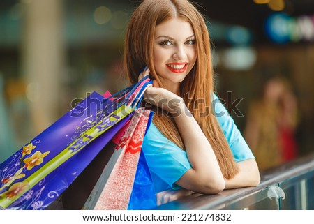 Happy woman shopping and holding bags at the mall. Shopping woman at the mall holding bags. Excited shopping woman holding bags with arms up - stock photo