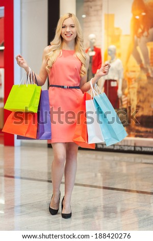 Happy woman shopping. Full length of young beautiful shopping woman smiling with colorful bags at mall center - stock photo