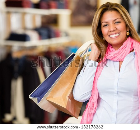 Happy woman shopping holding bags and smiling - stock photo