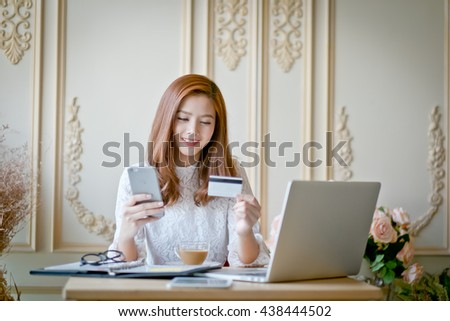 Happy woman shopping online, holding credit card, using laptop computer, electronic purchase. - stock photo