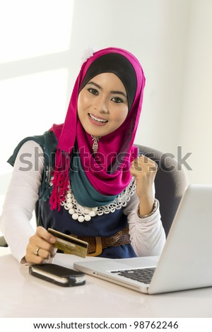 Happy woman shopping online with credit card and computer.Internet shopping - stock photo