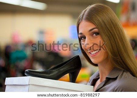 Happy woman shopping shoes in store; she is buying pumps - stock photo