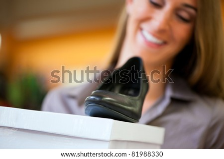 Happy woman shopping shoes in store; she is buying pumps (focus on shoes) - stock photo
