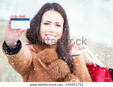 Happy woman shopping with her credit card in winter day - stock photo