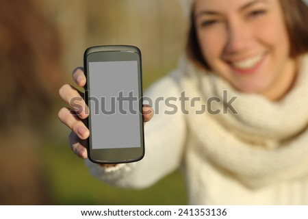 Happy woman showing a blank smart phone screen outdoors in winter - stock photo