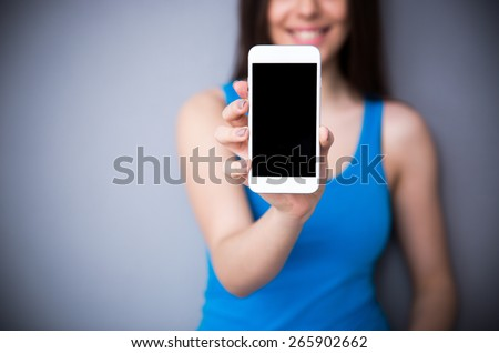Happy woman showing blank smartphone screen over gray background. Focus on smartphone. - stock photo