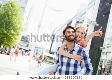 Happy woman showing something to man while enjoying piggyback ride in city - stock photo
