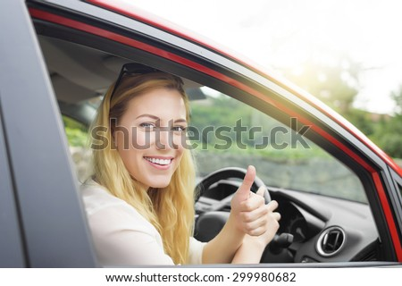Happy woman showing thumb up and driving a new car. - stock photo