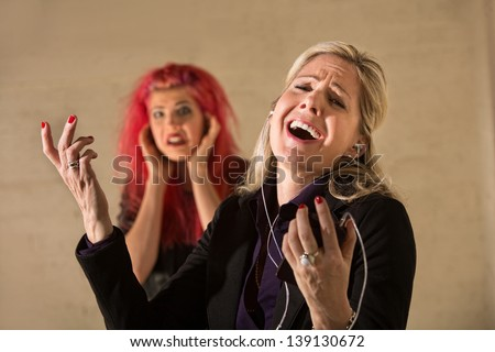 Happy woman singing loudly with annoyed teenager nearby - stock photo