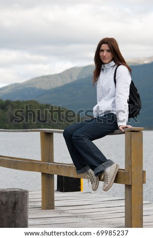 Happy woman sits on wood pier in front of mountains - stock photo