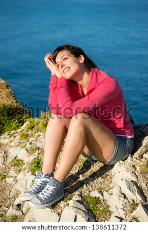 Happy woman sitting and relaxing on nature with sea landscape background. Day dreaming girl enjoying peace and silence on coast summer vacation. - stock photo