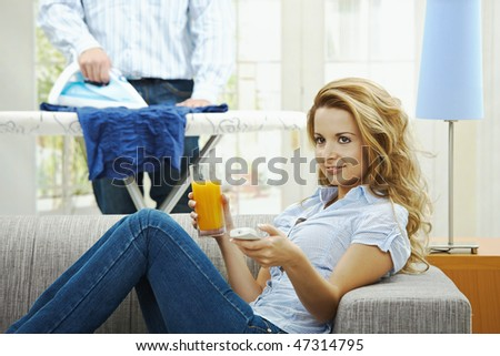 Happy woman sitting at couch watching TV, man ironing in the background. Selective focus on woman. - stock photo