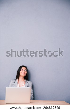 Happy woman sitting at the table with laptop and looking up at copyspace - stock photo