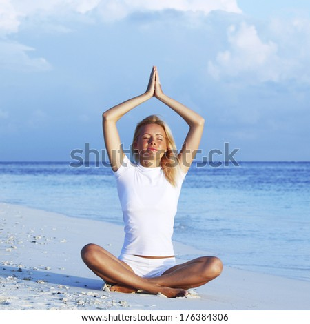 Happy woman sitting in yoga pose at the beach
