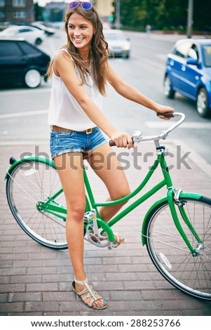 Happy woman sitting on bicycle by city road