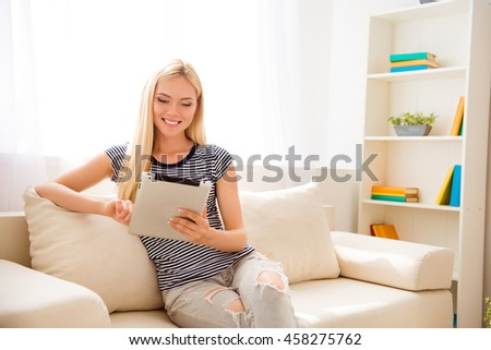 Happy woman sitting on couch and reading news on tablet - stock photo