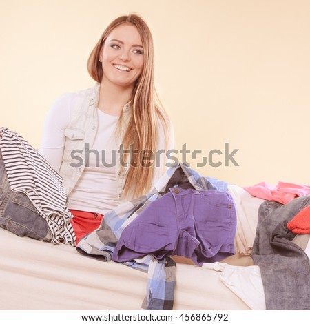 Happy woman sitting on sofa couch in messy living room. Young girl surrounded by many stack of clothes. Disorder and mess at home. - stock photo