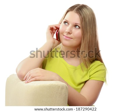 Happy woman sitting on sofa using mobile phone isolated on white background - stock photo