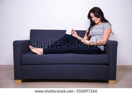happy woman sitting on sofa with phone and mug of tea or coffee - stock photo