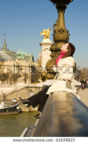 Happy woman sitting on the balustrade of the Pont Alexandre III in Paris - stock photo