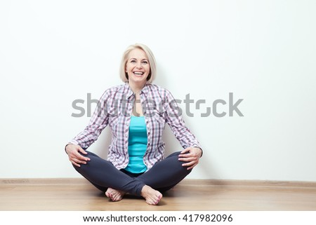 Happy woman sitting on the floor with crossed legs in fashionable clothing on white background in studio
