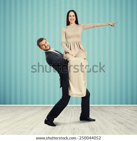 happy woman sitting on the man and pointing at something. photo in room with blue wall - stock photo