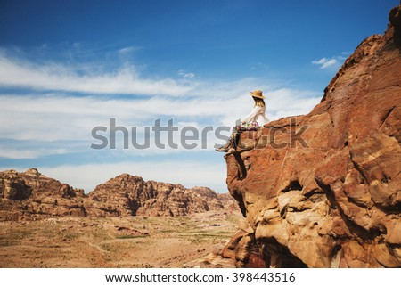 Happy woman sitting on the rock edge , enjoying stunning view.  Tourist   girl  in straw hat explore mountain valley . Bright blue sky.