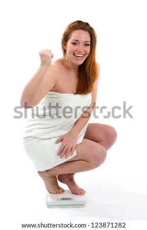 Happy woman smiling about the results on the bathroom scale of the amount of her losing weight.