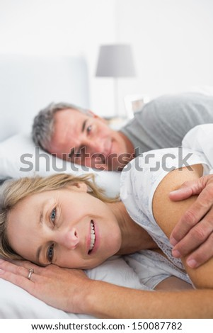 Happy woman smiling at camera with husband in bedroom at home