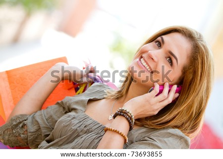 Happy woman smiling on the phone with shopping bags - stock photo