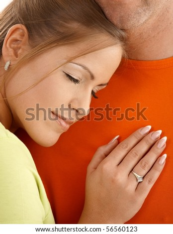 Happy woman smiling with eyes closed leaning on man's chest.