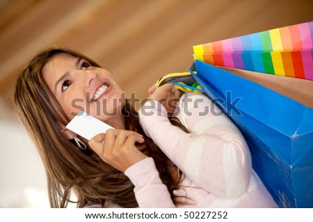 happy woman smiling with shopping bags and holding a credit card in a mall - stock photo